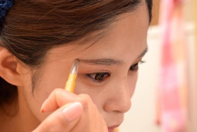 アイブロウペンシルを塗る女性